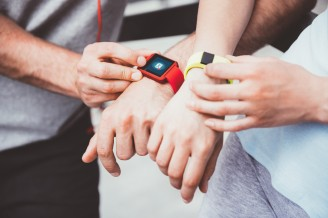 Athletic people sharing workout data from their smartwatches.